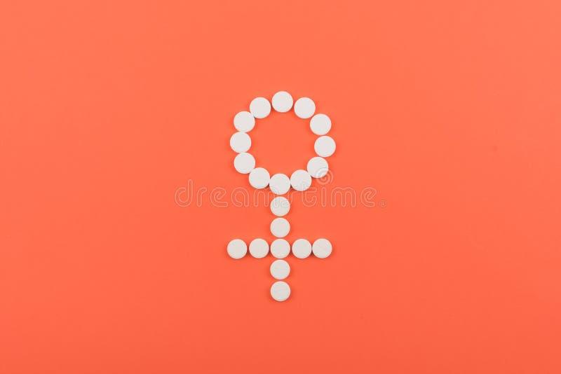 Comprimidos de controlo da natalidade, contraceptivo oral, método hormonal Comprimidos brancos sob a forma do símbolo fêmea do Vê imagem de stock royalty free