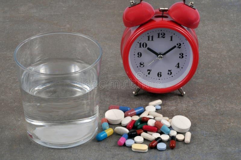 Comprimidos de sono ao lado de um vidro da água e de um despertador foto de stock