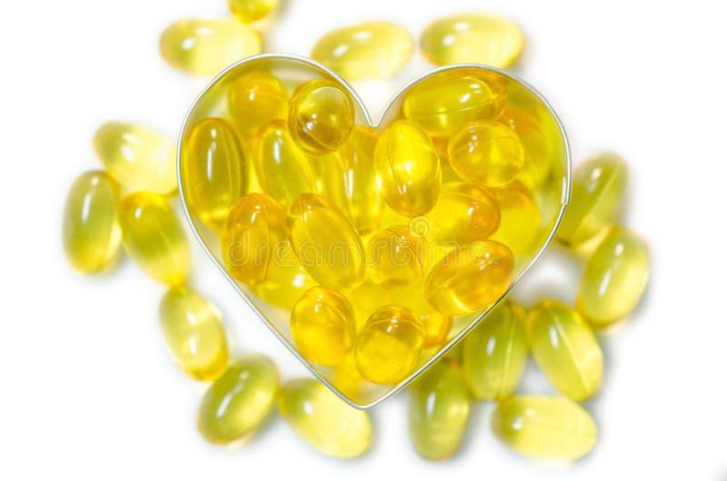 Comprimidos do óleo de peixes na caixa da forma do coração no fundo branco isolado fotografia de stock
