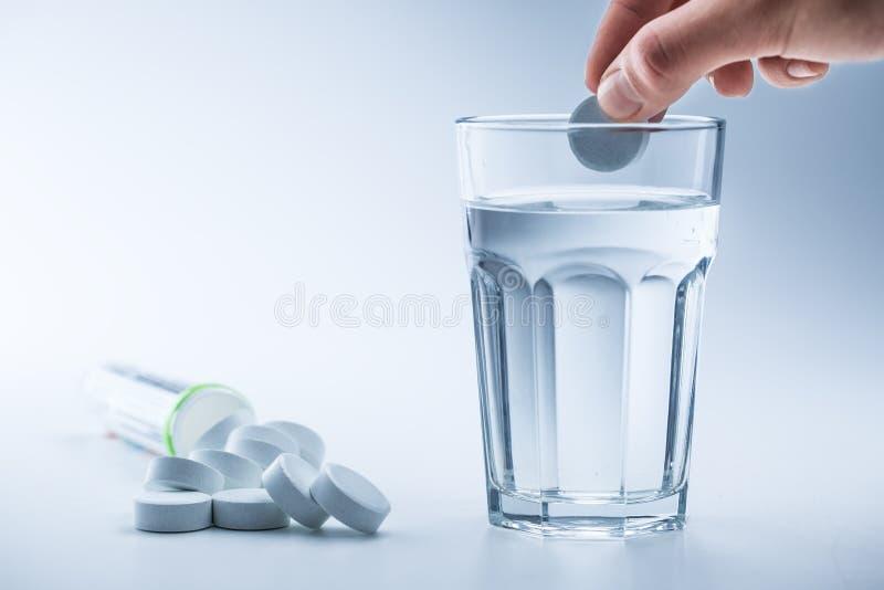 Comprimidos do magnésio e copo da água clara no fundo branco azul imagem de stock