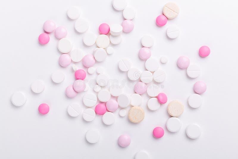 Comprimidos do rosa e os brancos no fundo branco Montão de várias tabuletas sortidos e de comprimidos da medicina Cuidados m?dico fotos de stock