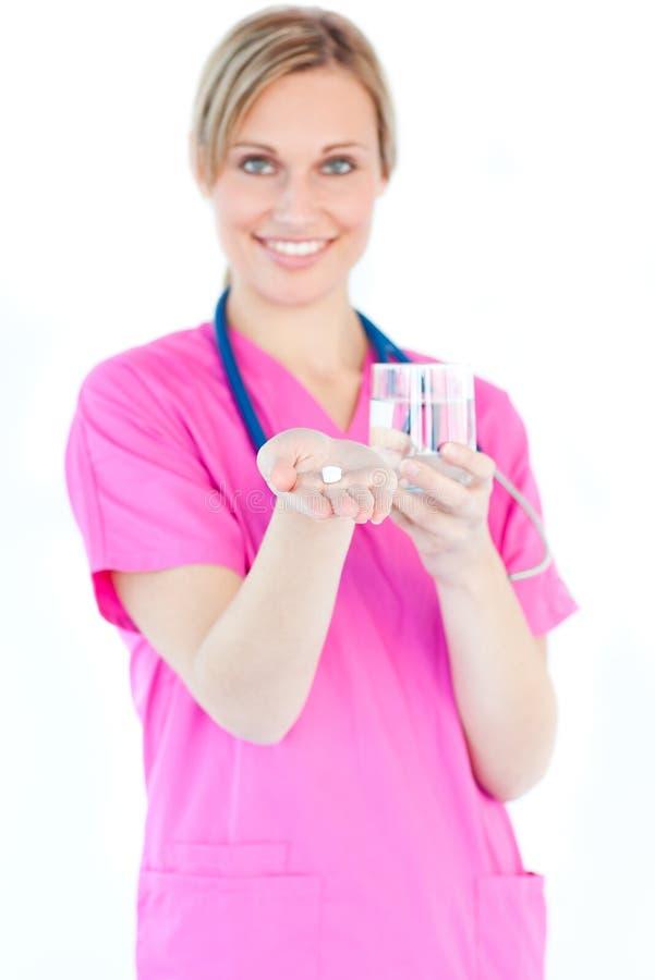 Comprimidos e água fêmeas brilhantes da terra arrendada da enfermeira fotos de stock