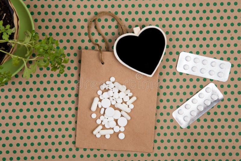 comprimidos e cápsulas brancas, saco de compras feito a mão, saco do presente e bl fotos de stock