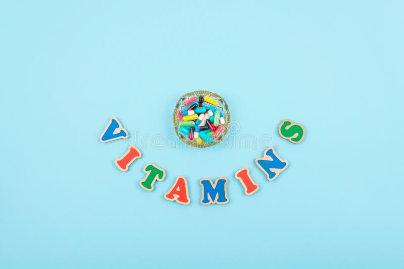 Comprimidos e cápsulas coloridas diferentes na placa redonda e palavra colorido VITAMINAS no fundo azul Suplemento à nutrição, dr fotos de stock