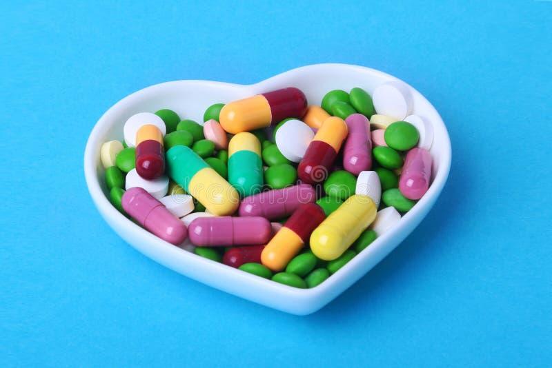Comprimidos e cápsulas coloridos da variedade na placa fotos de stock royalty free