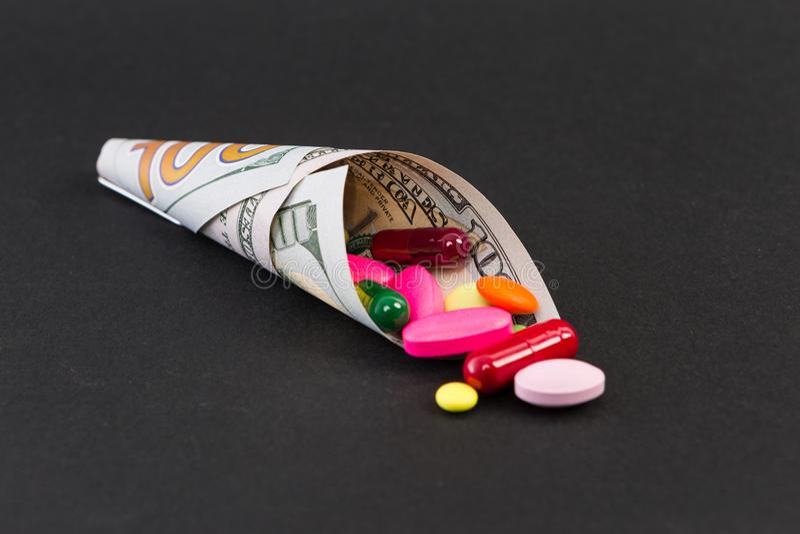 Comprimidos e cápsulas envolvidos em cem notas de dólar imagem de stock royalty free