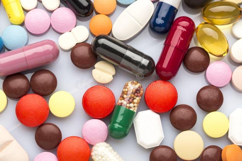 Comprimidos e cápsulas médicos coloridos dispersados fotografia de stock royalty free