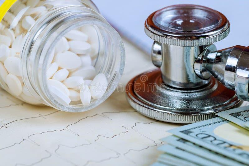 Comprimidos e dólares do estetoscópio do close-up com comprimidos sortidos Conceito saudável da vida ou do seguro fotos de stock