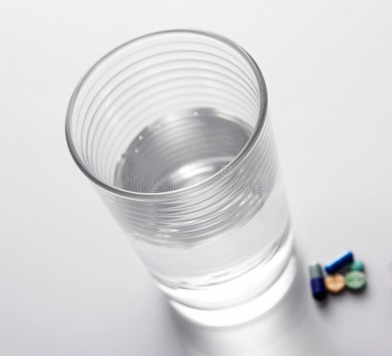 Comprimidos e um vidro da água fotos de stock