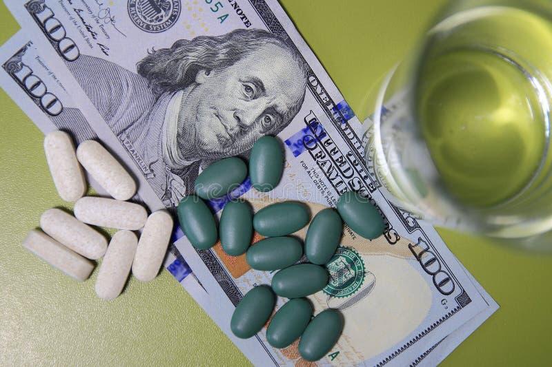 Comprimidos e vidro verdes brancos da água em cem notas de dólar Custo do conceito saudável da vida foto de stock royalty free