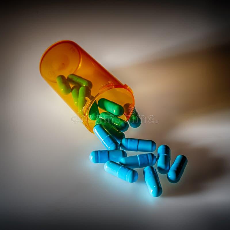 Comprimidos farmacêuticos que derramam fora de uma garrafa imagem de stock royalty free