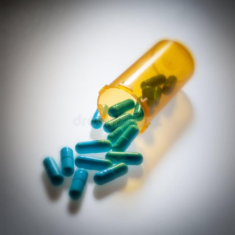 Comprimidos farmacêuticos que derramam fora de uma garrafa foto de stock