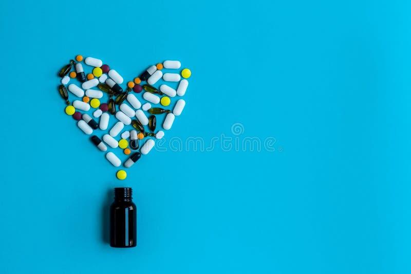 Comprimidos isolados que derramam fora da garrafa de comprimido Coração saudável foto de stock royalty free