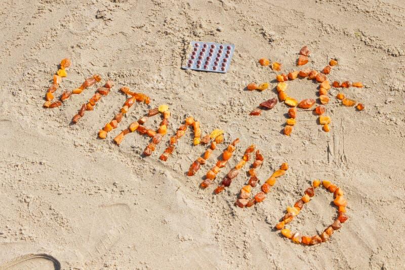 Comprimidos médicos, vitamina D da inscrição e forma do sol na praia, conceito das horas de verão e estilo de vida saudável fotografia de stock