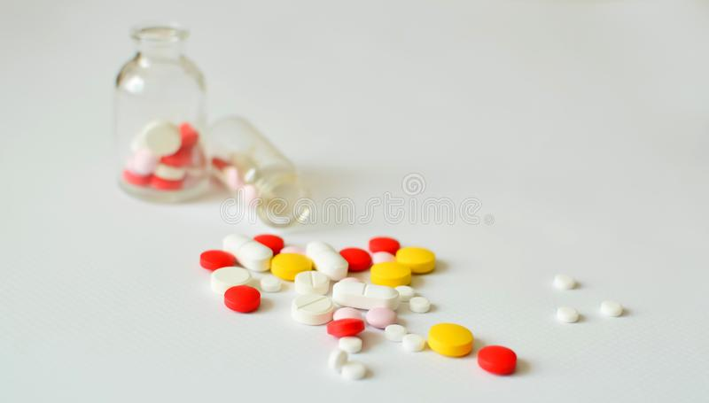 comprimidos Multi-coloridos em umas garrafas de vidro transparentes, em um fundo branco O conceito da medicina, tratamento imagem de stock royalty free