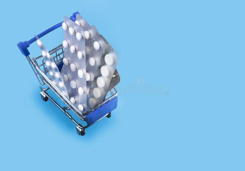 Comprimidos no carro Carrinho de compras carregado com os comprimidos no fundo azul O conceito da medicina e a venda das drogas C fotos de stock