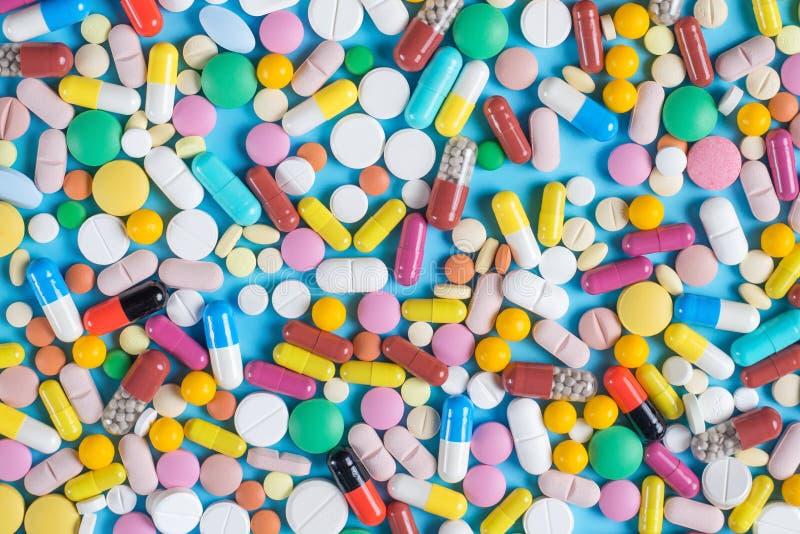 Comprimidos ou cápsulas verdes, amarelas, vermelhas e cor-de-rosa em um fundo azul fotografia de stock royalty free
