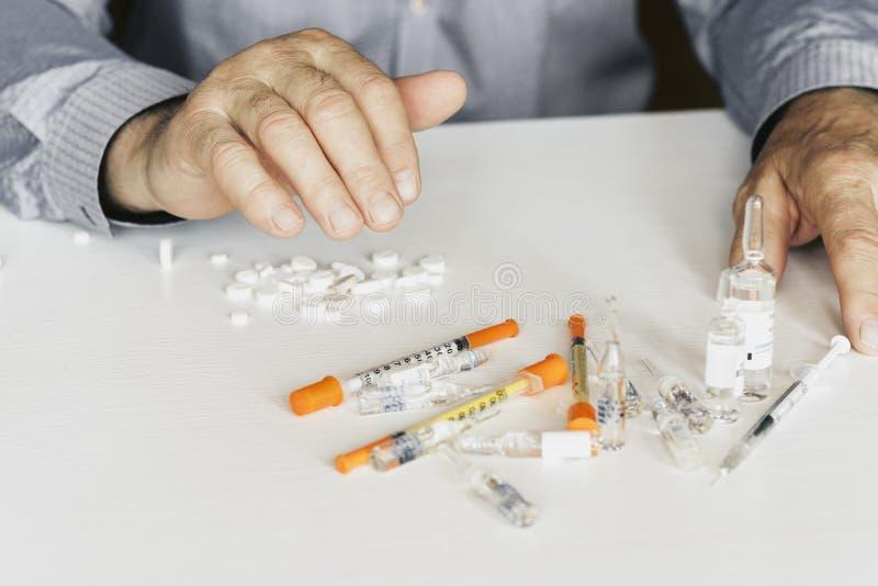 Comprimidos ou c?psulas da medicina com m?os dos man?s no fundo branco com espa?o da c?pia fotografia de stock royalty free