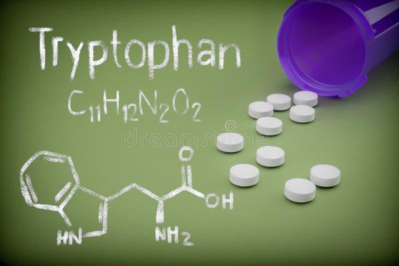 Comprimidos que derramam uma garrafa aberta no fundo verde, formulação química do trytophan escrita com giz imagem de stock