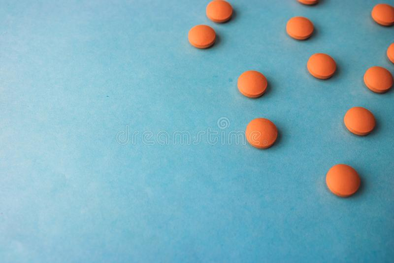 Comprimidos redondos pharmaceptic médicos bonitos da laranja amarela pequena, vitaminas, drogas, antibióticos em um fundo azul, t imagem de stock