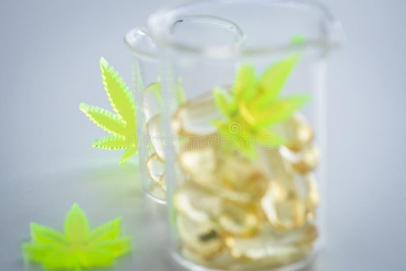 Comprimidos, tabuletas, c?psulas do c?nhamo da marijuana do cannabis e do CBD na ta?a de vidro da escala de laborat?rio como o as fotografia de stock royalty free