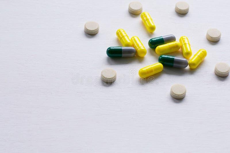 Comprimidos, tabuletas e cápsulas em um fundo branco O conceito da medicina, da farmácia e dos cuidados médicos imagem de stock