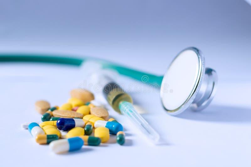 Comprimidos, tabuletas e cápsulas farmacêuticos coloridos da medicina com seringa e estetoscópio no fundo branco Conceito MÉDICO foto de stock