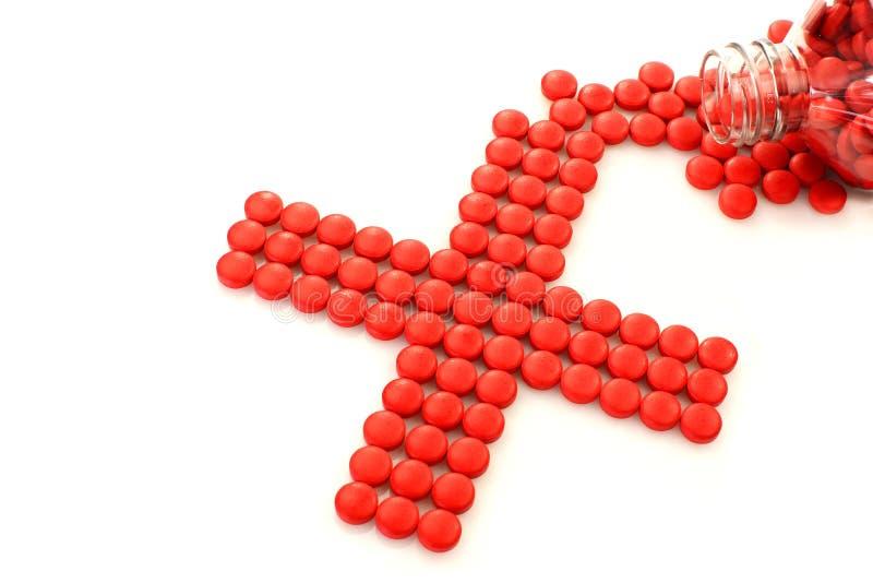 Comprimidos vermelhos que dão forma a uma cruz vermelha fotografia de stock