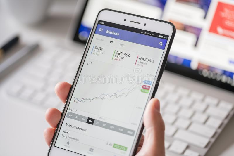 Comprobación de datos del mercado de acción sobre un smartphone fotos de archivo
