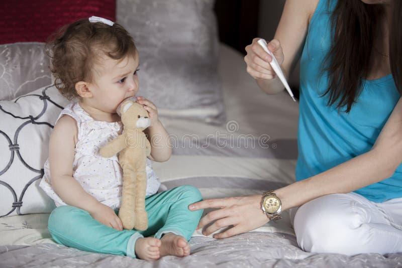 Comprobación de la temperatura del bebé foto de archivo libre de regalías