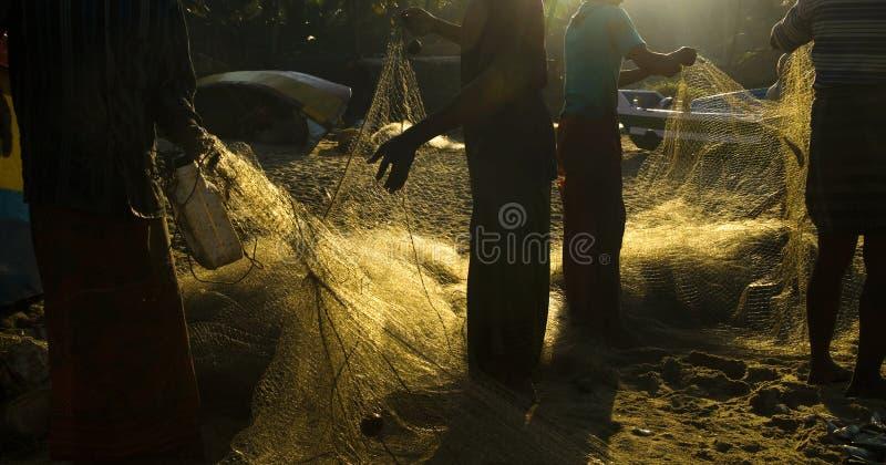 Comprobación de las redes de pesca en la salida del sol imagen de archivo libre de regalías