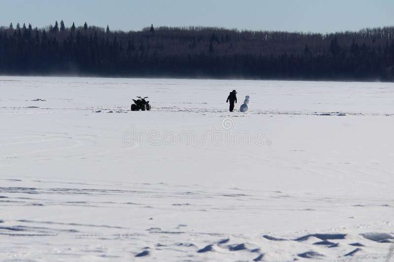 Comprobación hacia fuera de un muñeco de nieve solo en el medio de un lago congelado foto de archivo