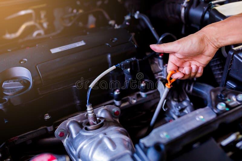 Compruebe el nivel de aceite en motor de coche Mecánico Checking Car Engine foto de archivo