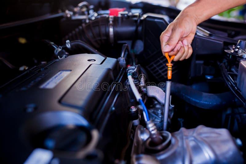 Compruebe el nivel de aceite en motor de coche Mecánico Checking Car Engine imagenes de archivo