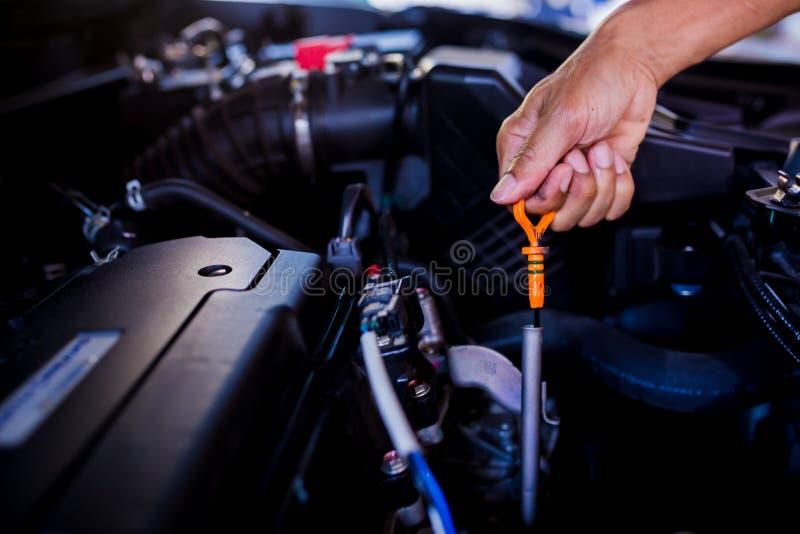 Compruebe el nivel de aceite en motor de coche Mecánico Checking Car Engine fotografía de archivo libre de regalías