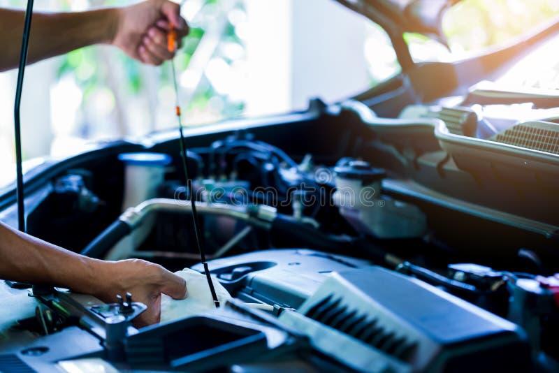 Compruebe el nivel de aceite en motor de coche Mec?nico que comprueba el motor o el veh?culo de coche foto de archivo