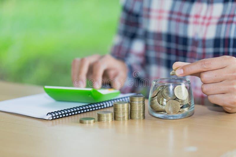 Comptabilité d'entreprise avec l'argent d'économie avec la main mettant des pièces de monnaie en verre de cruche, homme d'affaire images stock