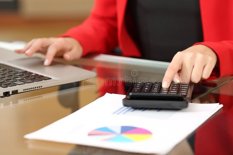 Comptabilité de femme d'affaires avec la calculatrice et l'ordinateur portable photographie stock