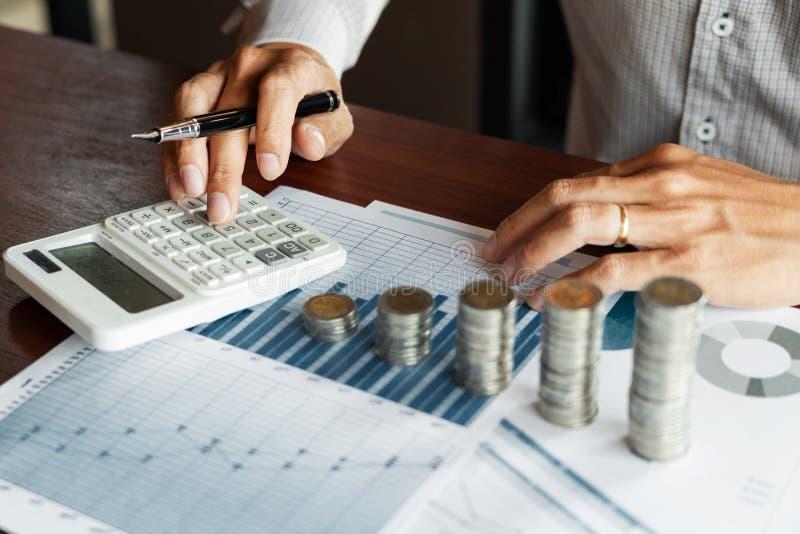 Comptable Calculating d'homme d'affaires sur les documents de donn?es et la pile de pile de pi?ces de monnaie, l'investissement d photographie stock
