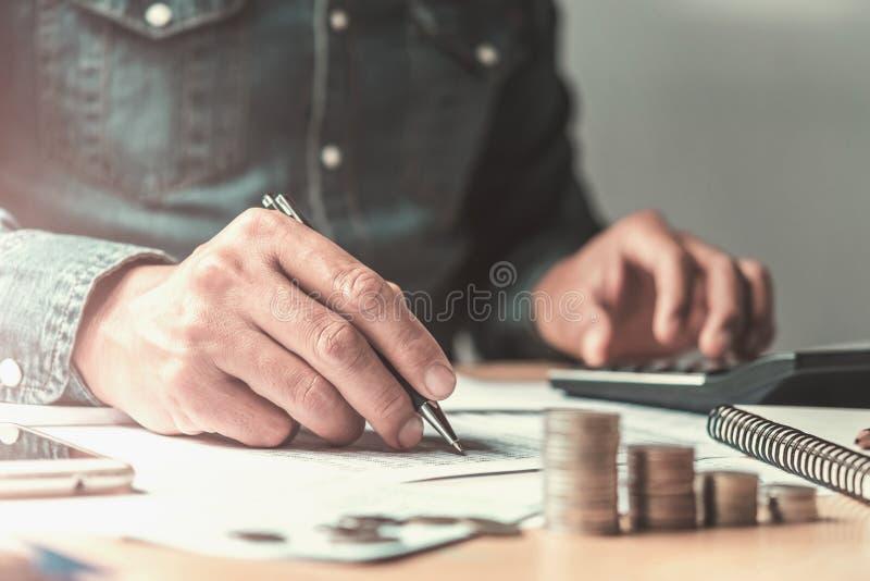comptable employant le stylo et calculatrice fonctionnant avec le document dedans  photo stock
