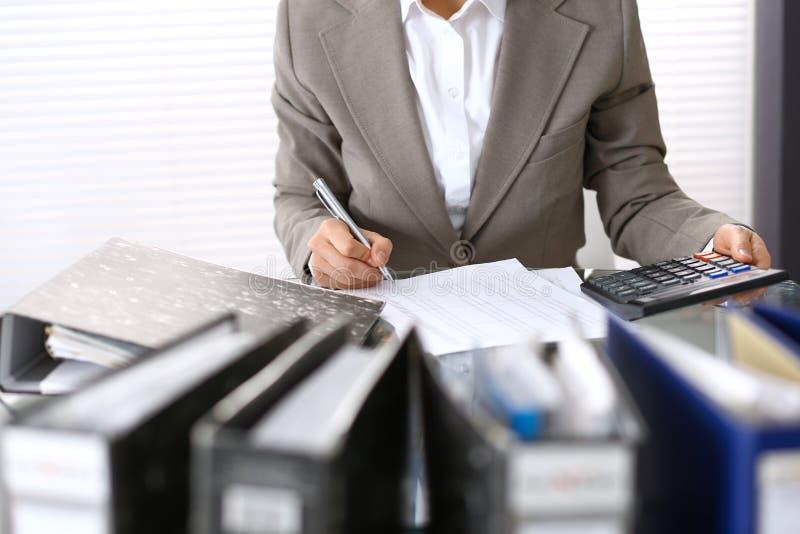 Comptable féminin ou inspecteur financier rédigeant le rapport, calculant ou vérifiant l'équilibre Recettes Servic photo stock