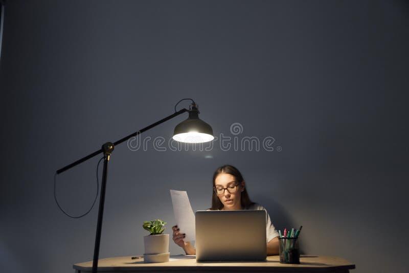Comptable féminin surchargé travaillant sur l'ordinateur portable tard à photographie stock libre de droits