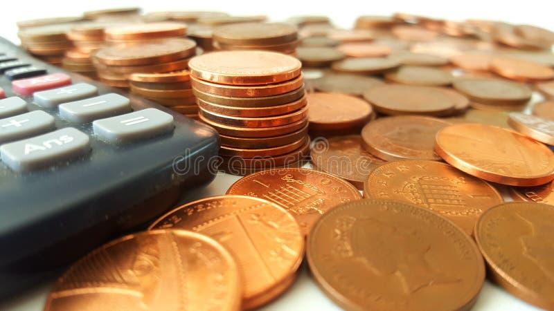 Comptant les penny - piles de penny près d'une calculatrice photo stock