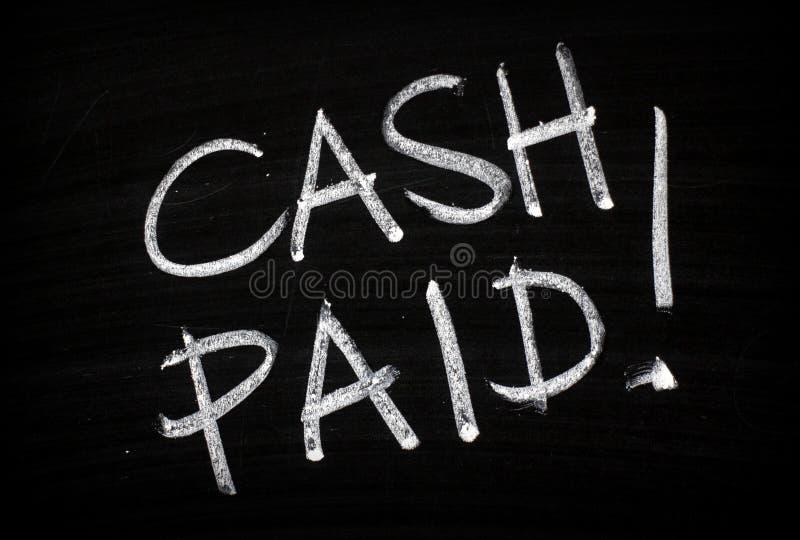 Comptant payé écrit sur un tableau noir image stock