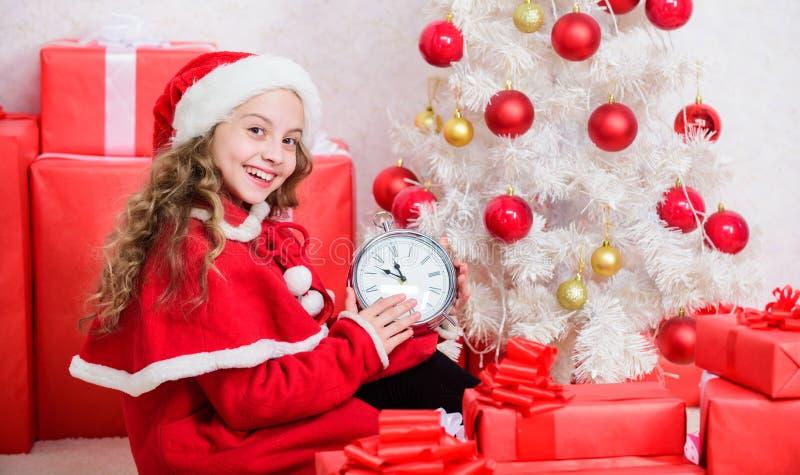 Compte à rebours de la nouvelle année La petite fille santa chapeau tenir une horloge heureux visage excité le temps de compter l images stock