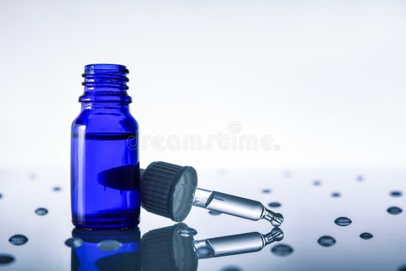 Compte-gouttes sur la table en verre avec le contre-jour bleu de fond de baisses photo stock