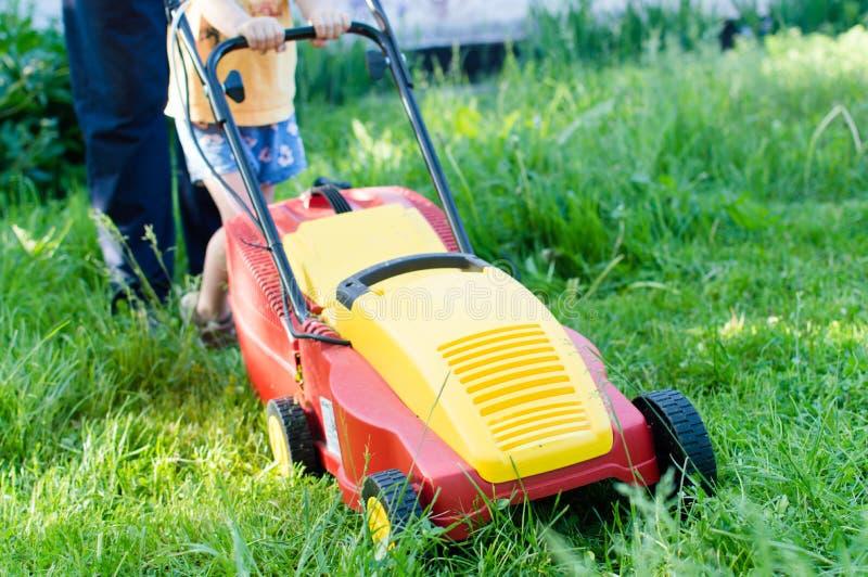 Comptes de chaque petits aide : image du règlage d'herbe ou la machine de moteur de pelouse fonctionnant ou poussant par le petit photo stock