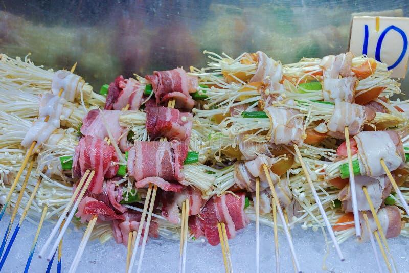 Compteur de nourriture de rue, barbecue de champignons, petit pain de champignon avec le lard, paquets d'enoki avec de la viande image stock