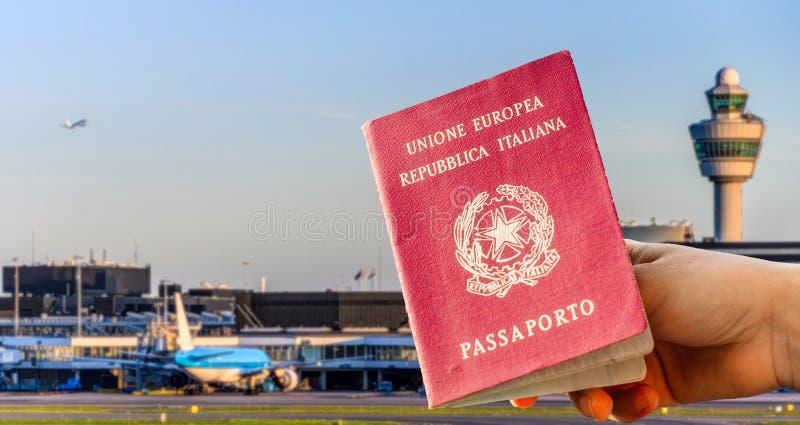 Compuesto de Digitaces de la mano que sostiene un pasaporte italiano con termina ocupado del aeropuerto imágenes de archivo libres de regalías
