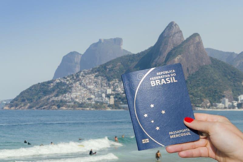 Compuesto de Digitaces que sostiene el pasaporte brasileño con Rio de Janeiro, Brazi fotos de archivo